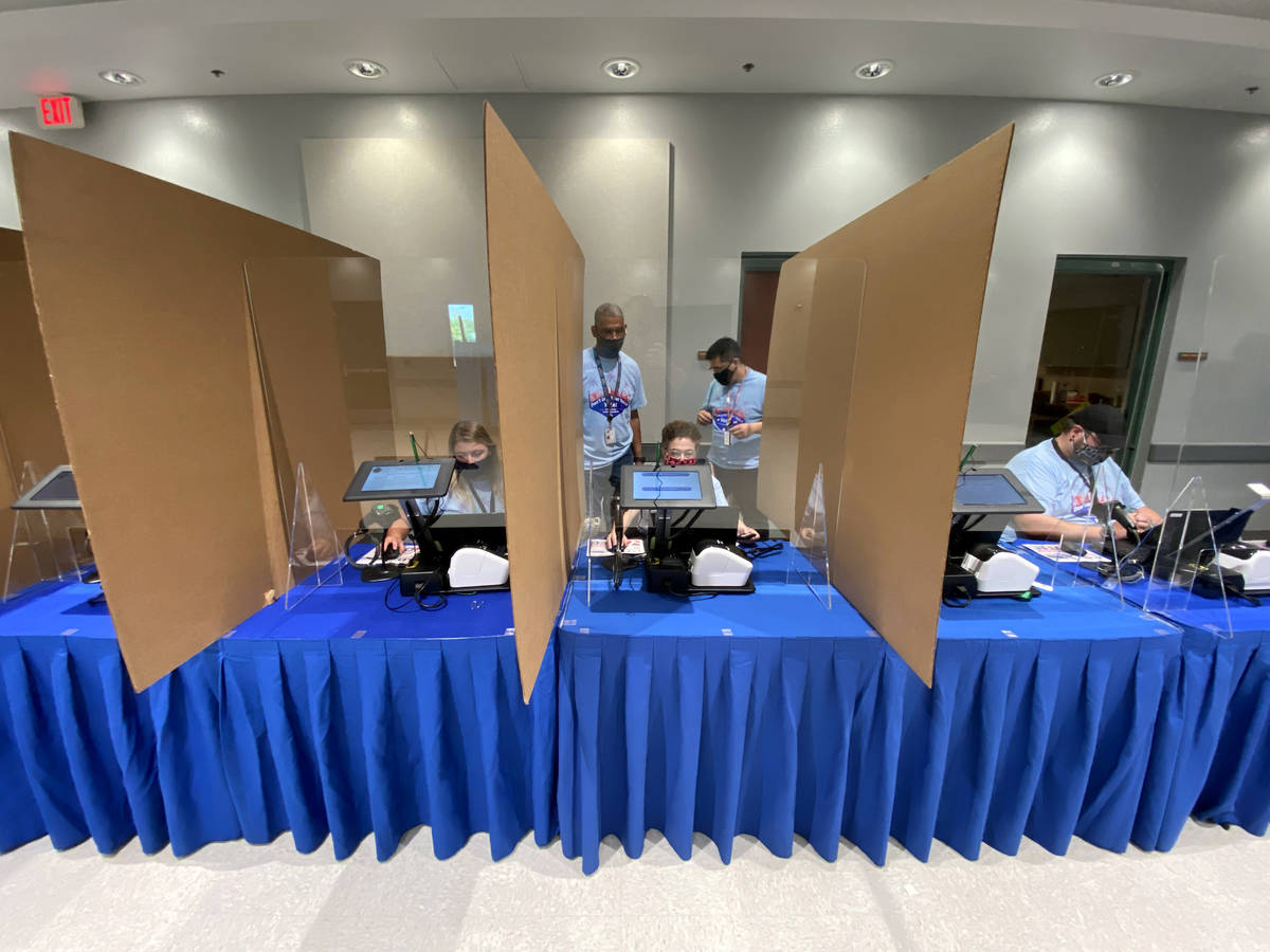 Clark County election workers set up cardboard and plexiglass barriers at registration kiosks a ...