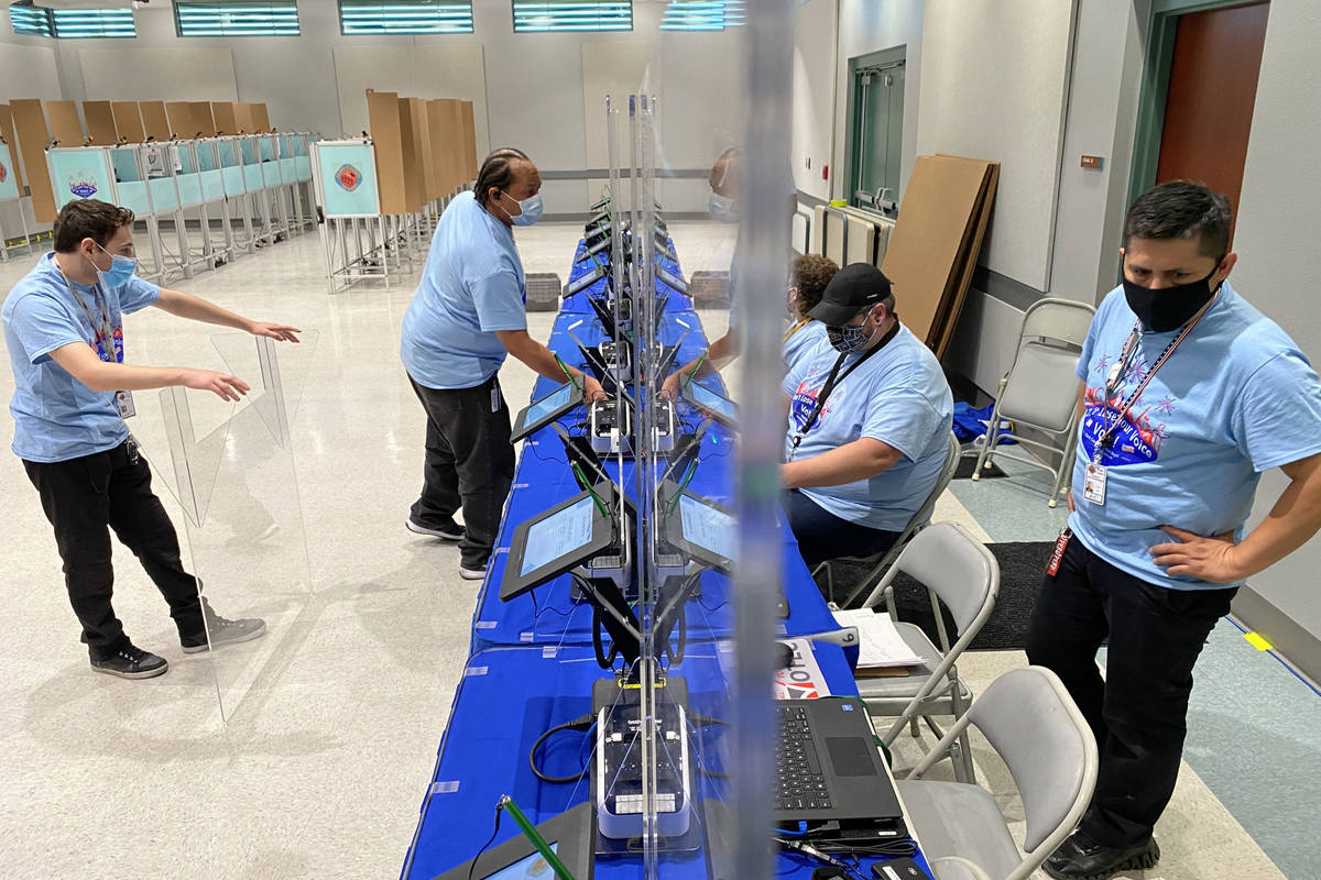 Clark County election workers set up plexiglass barriers at registration kiosks at the Cora Col ...
