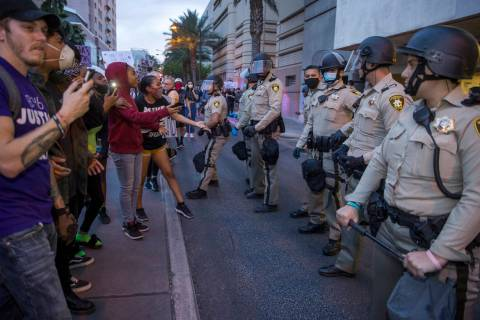 Las Vegas police look on as protesters confront them while marching along Casino Center Drive d ...