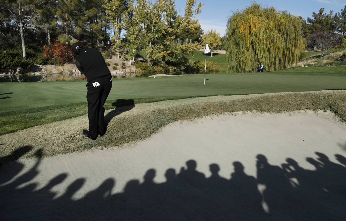 Phil Mickelson hits onto the fourth green during a golf match against Tiger Woods at Shadow Cre ...