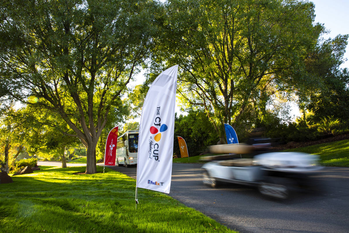 A golf cart and shuttle pass by signage for the CJ Cup at the Shadow Creek Golf Course in North ...