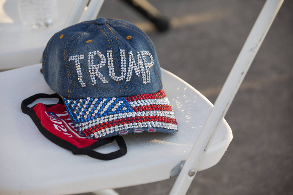 A hat and face mask acts as a seat holder at a campaign event for President Trump on Wednesday ...