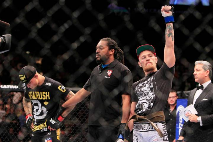 Wearing his new brown belt, Conor McGregor raises his arm after scoring a first round TKO of Du ...