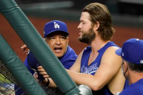 Los Angeles Dodgers manager Dave Roberts talks with starting pitcher Clayton Kershaw before Gam ...