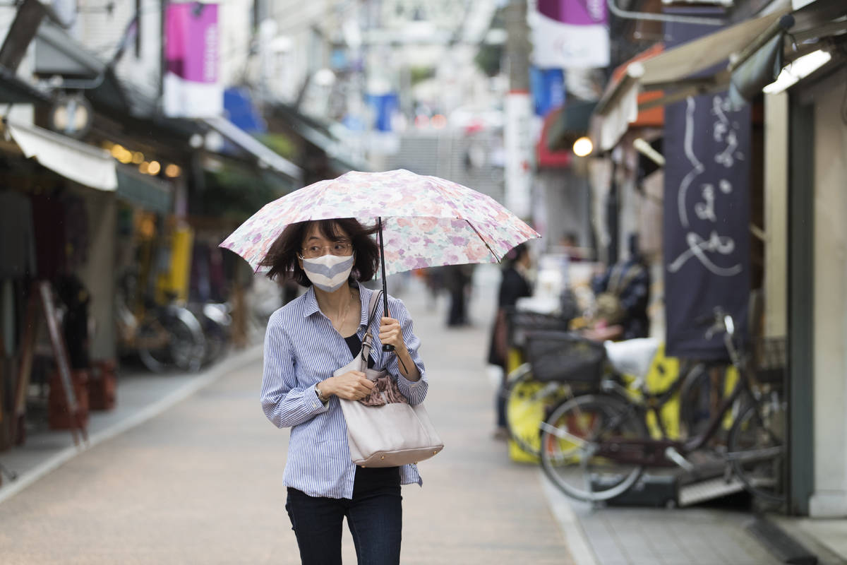 A woman with a face mask walks through a shopping street in the rain in Tokyo on Thursday, Oct. ...