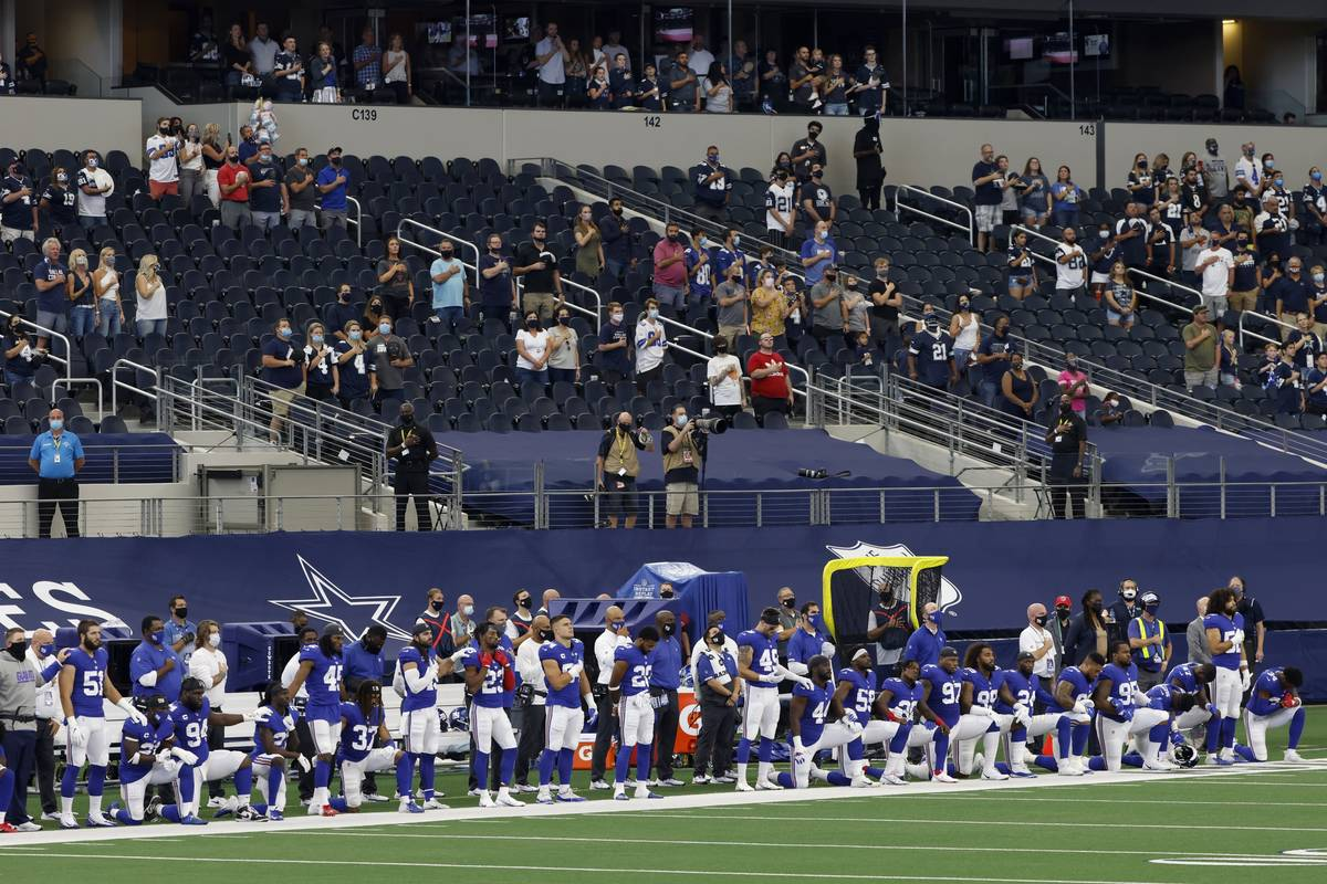 Players and staff of the New York Giants stand and kneel as they and fans in attendance listen ...