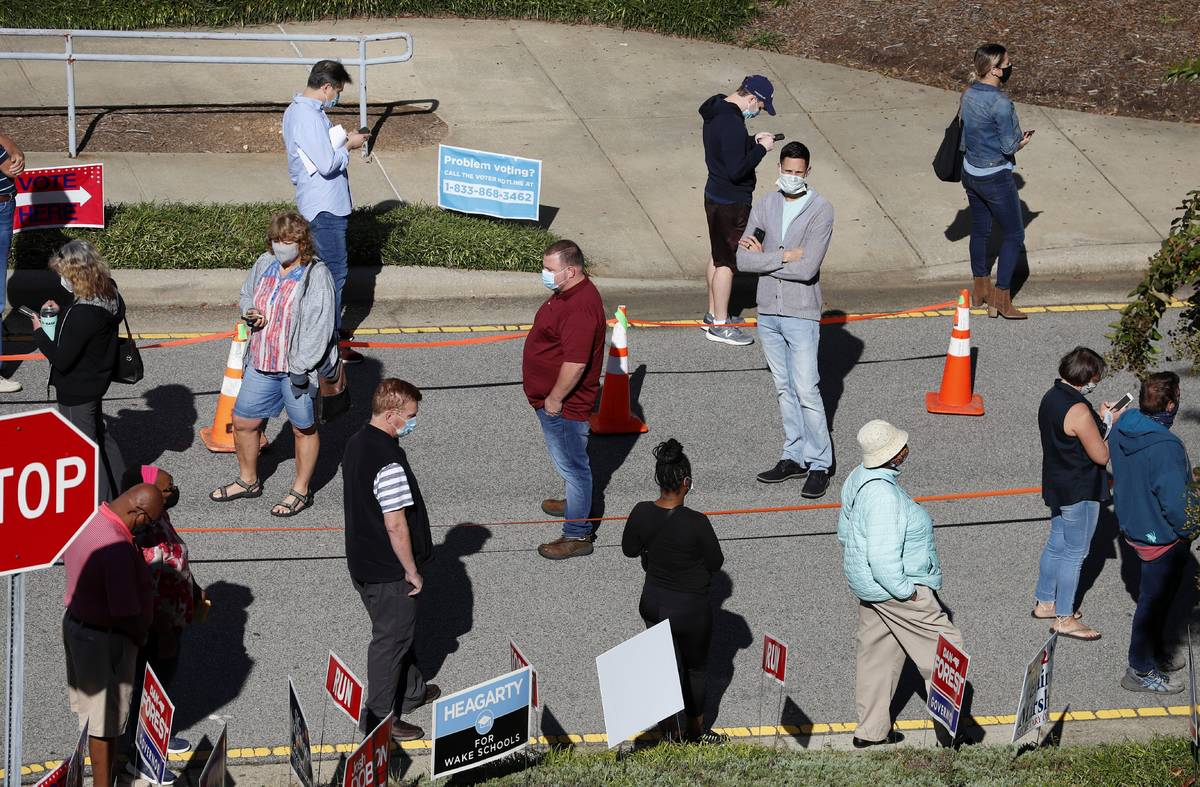Voters wait in line outside the Herbert C. Young Community Center in Cary, N.C. on the first da ...