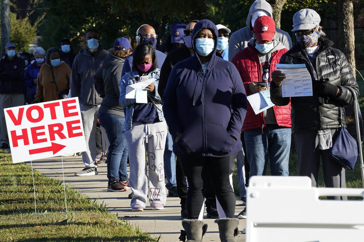 Early voters line up to cast their ballots at the South Regional Library polling location in Du ...
