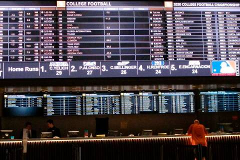 In this June 27, 2019 photo, a gambler places a bet at the new sportsbook at Bally's casino in ...
