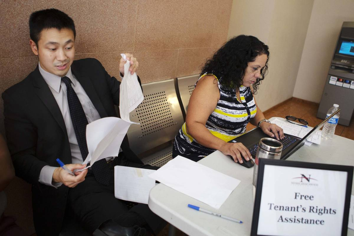 Nevada Legal Services Attorney Ron Sung, left, looks over eviction processing paperwork as para ...