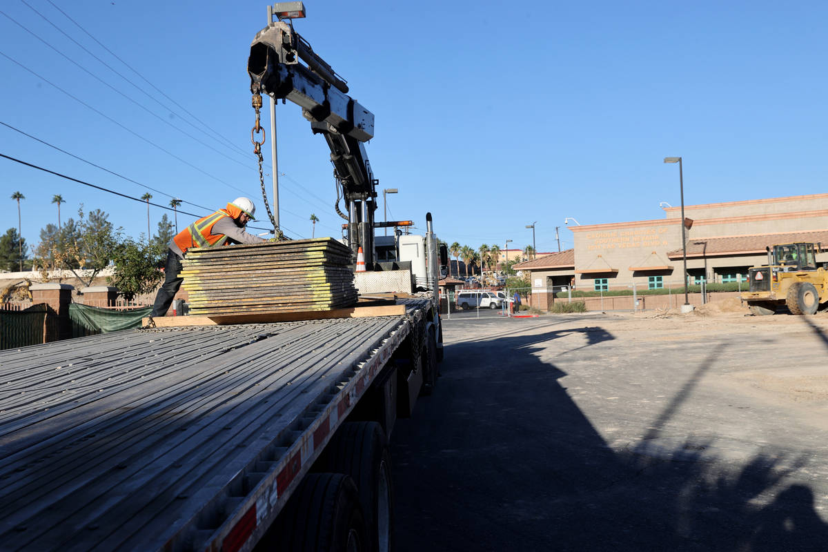 A worker unloads metal plates a former landscaped area at Catholic Charities of Southern Nevada ...