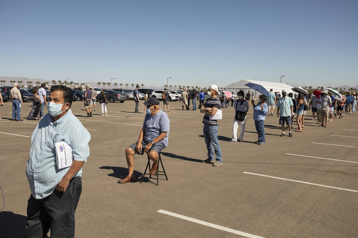 Individuals stand in line to early vote at the event tent located at Downtown Summerlin Las Veg ...