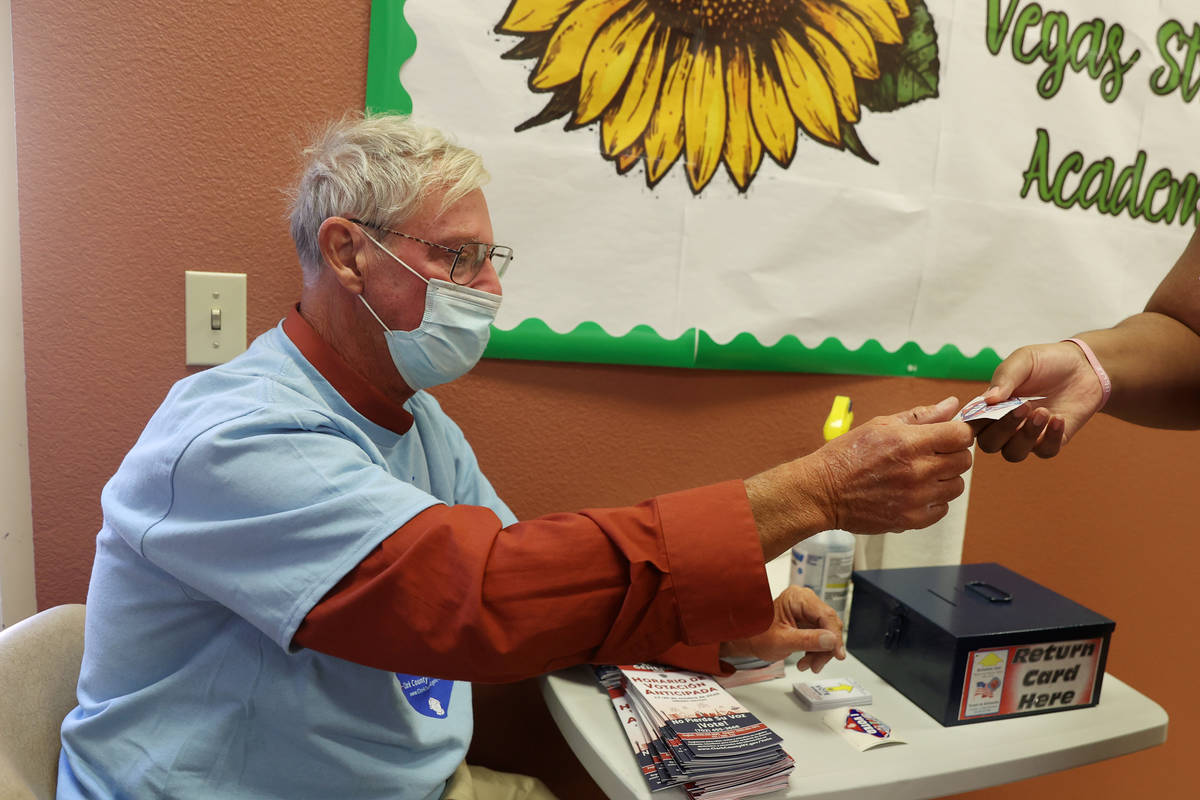 Poll worker Michael Brower hands out stickers to voters at the East Las Vegas Community Center ...