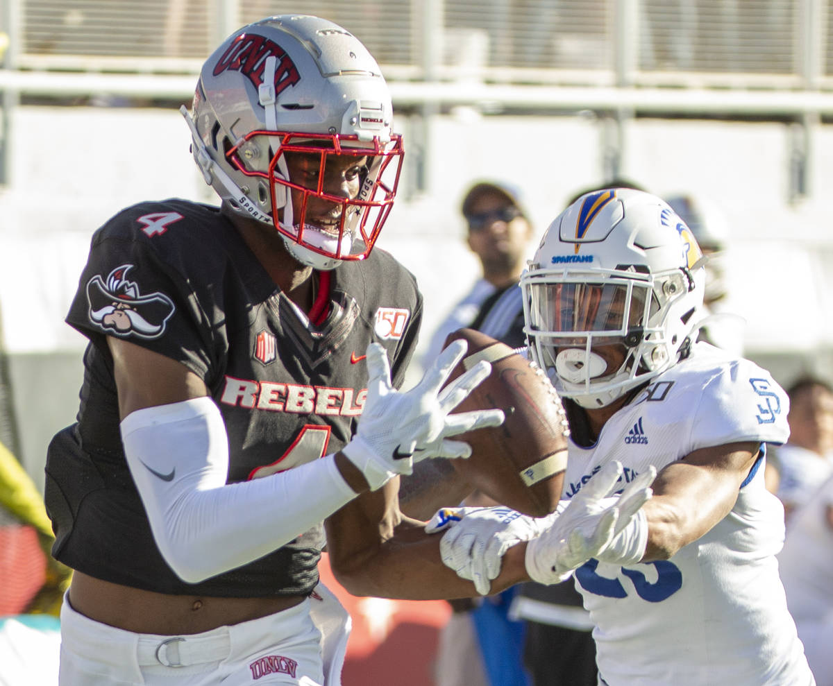 UNLV Rebels wide receiver Randal Grimes (4, left) eyes a long pass for a touchdown over the San ...
