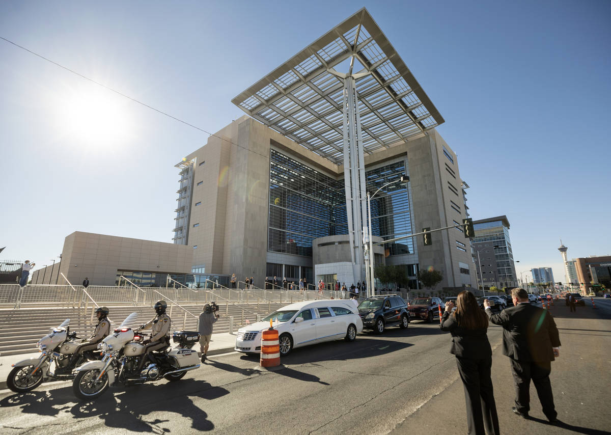 A police-escorted motorcade arrives at the front of the Lloyd D. George Federal Courthouse to h ...