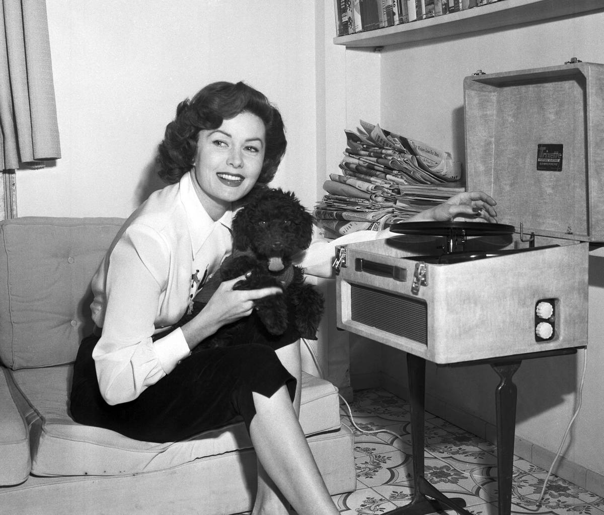 FILE - In this March 1, 1955 file photo, Actress Rhonda Fleming reads in her penthouse apartmen ...