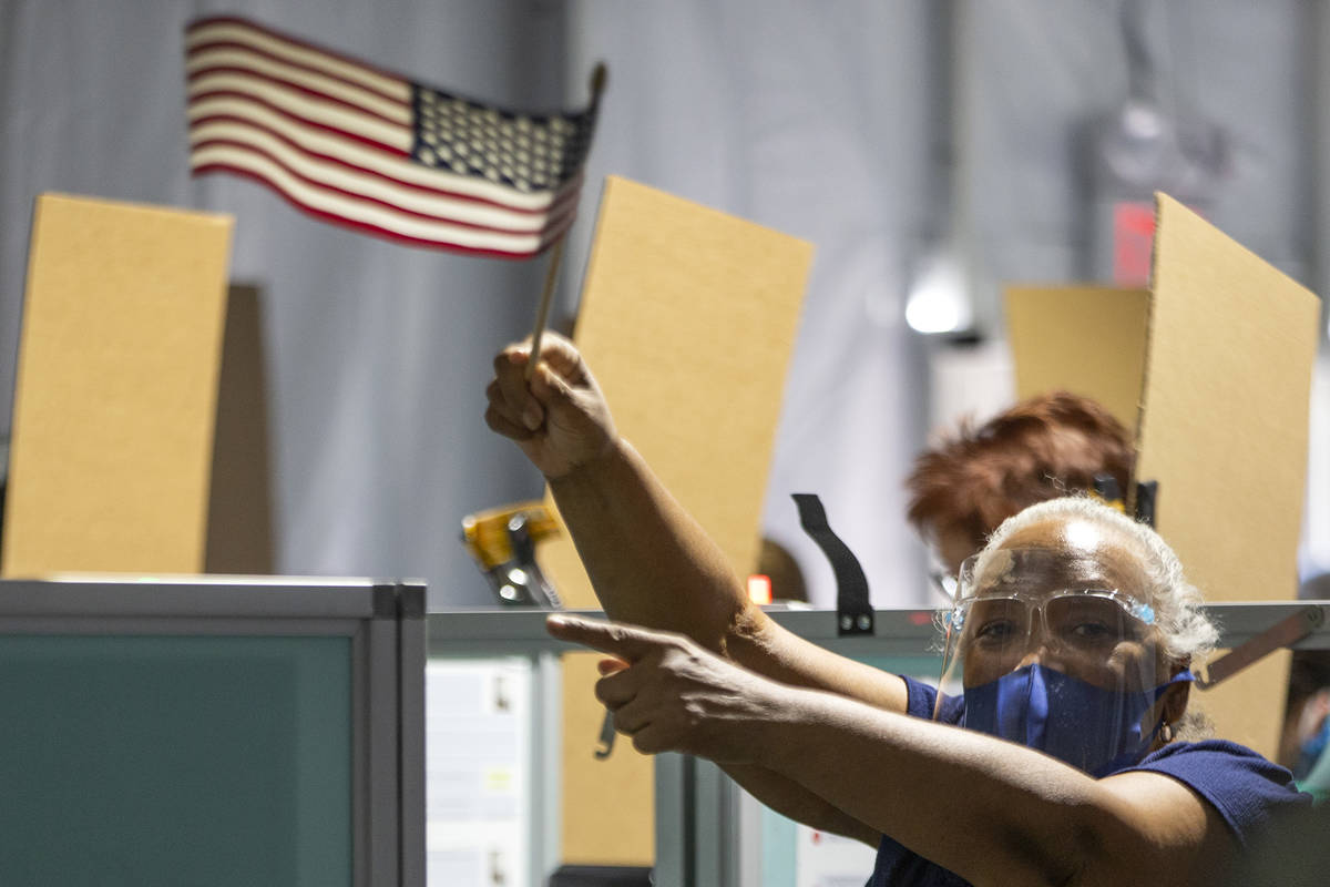 Poll worker Tamara Nash guides voters to empty spaces with an American flag at the Boulevard Ma ...
