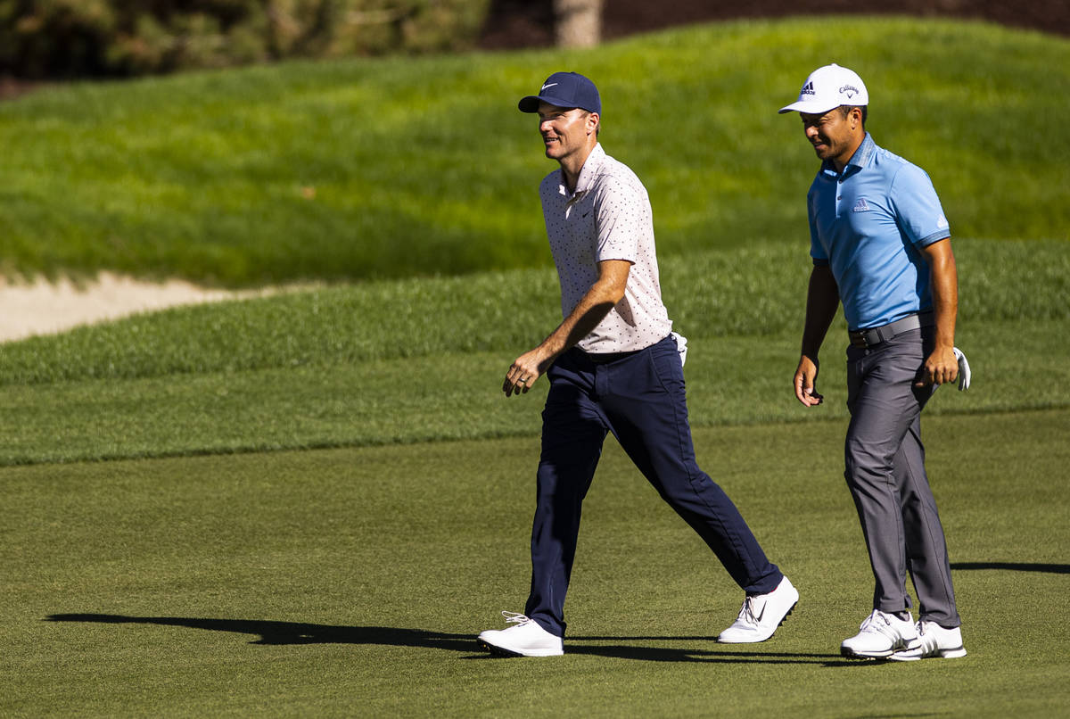 Russell Henley, left, talks with Xander Schauffele as they walk on the fairway at the 12th hole ...