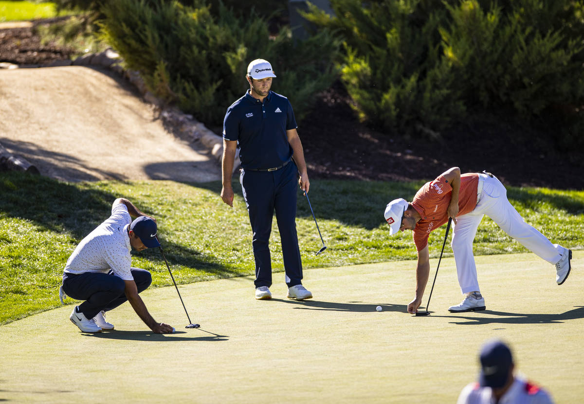 Jason Day, from left, Jon Rahm, and Andrew Landry prepare for putt shots at the 13th green duri ...