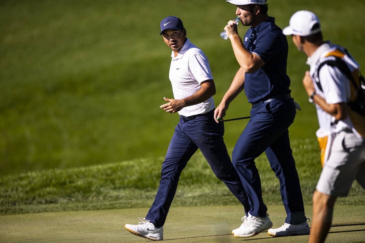 Jason Day, left, talks with Jon Rahm as they walk toward the 13th green during the third round ...