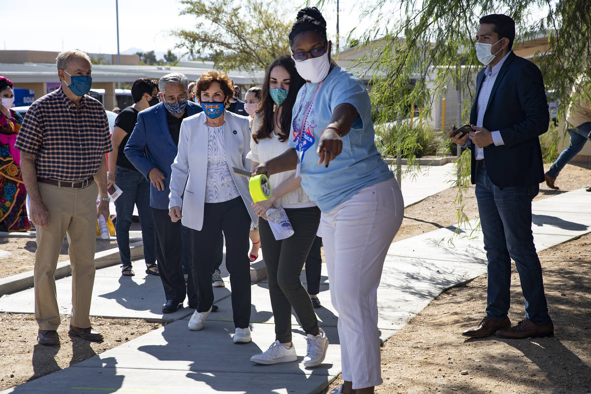 Sen. Jacky Rosen, D-Nev., is led to the voting booth by staff after speaking at an event to pro ...