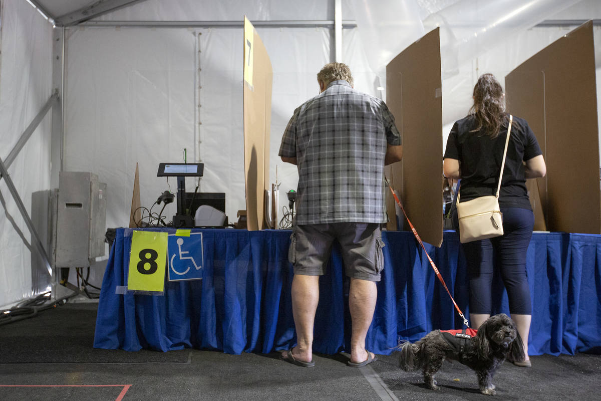 Voters cast their ballots at the Meadows Mall early voting location on Sunday, Oct. 18, 2020, i ...