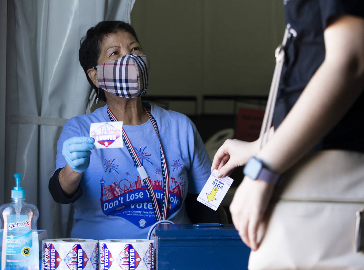 """Wilma Dal Mundo, who has been a poll worker for 13 years, hands out """"I Voted"""" sticker ..."""