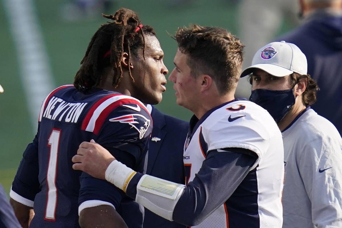 New England Patriots quarterback Cam Newton, left, speaks to Denver Broncos quarterback Drew Lo ...