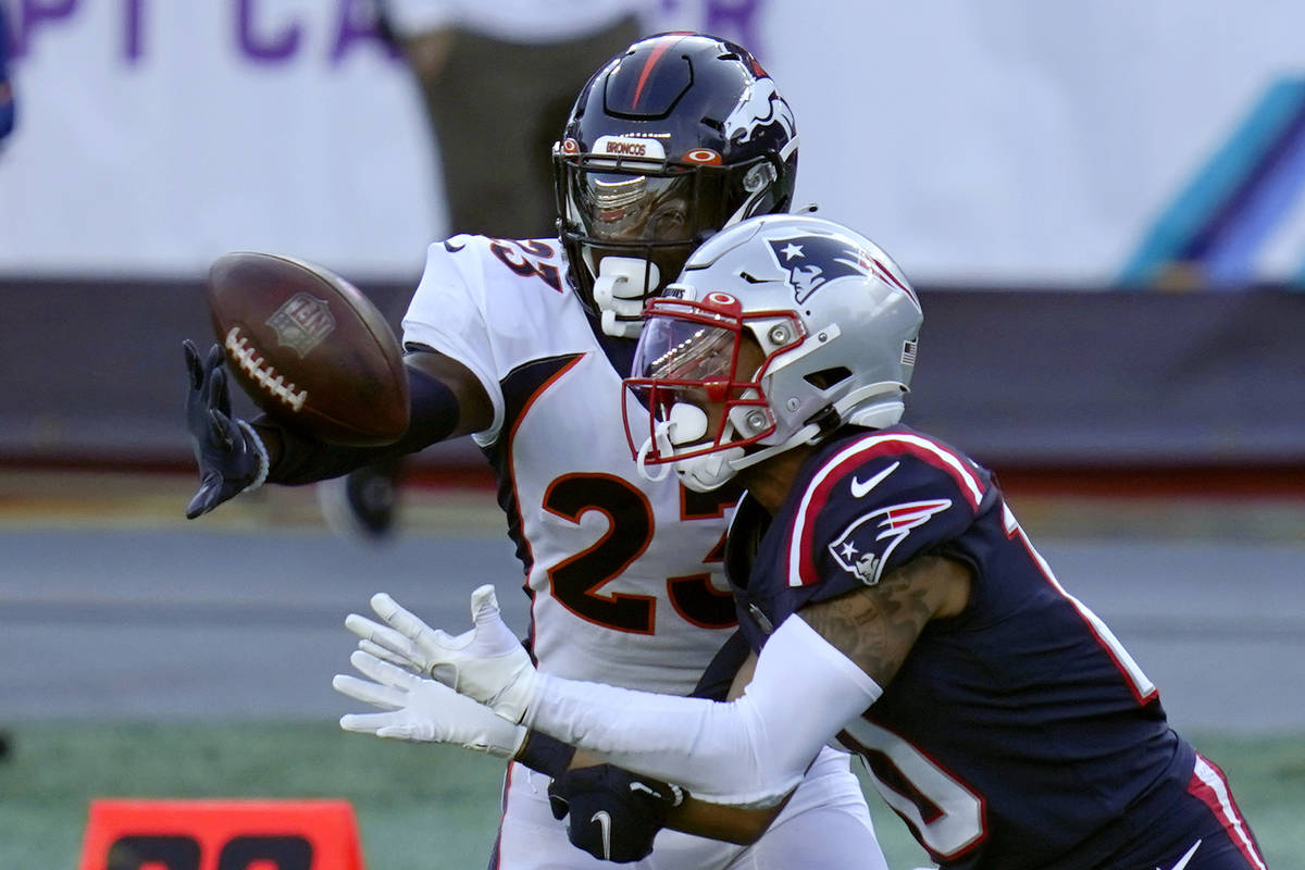 Denver Broncos cornerback Michael Ojemudia, rear, breaks up a pass intended for New England Pat ...