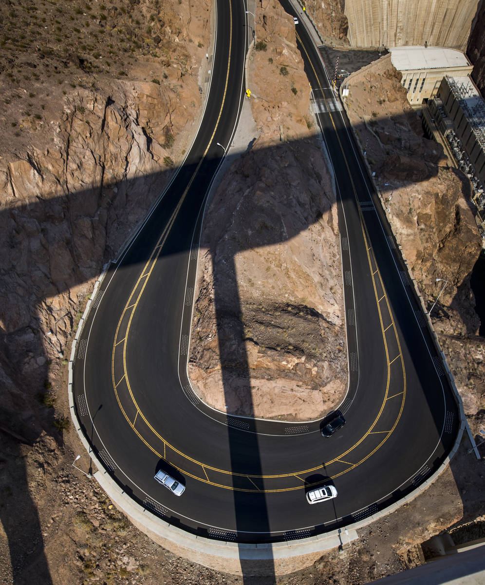 A few vehicles round the curve as Hoover Dam opens up to the public after being closed for mont ...