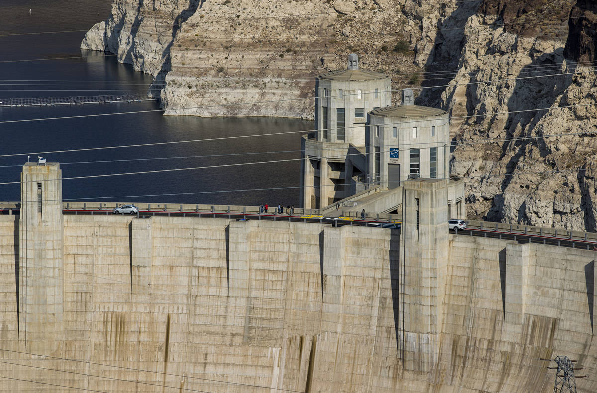 Visitors walk along the top of the Hoover Dam now open to the public after being closed for mon ...