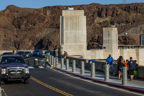 Visitors walk along the top of Hoover Dam, which reopened to the public after being closed for ...