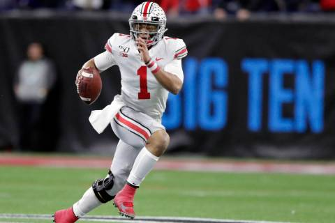 In this Dec. 7, 2019, file photo, Ohio State quarterback Justin Fields (1) runs with the ball a ...