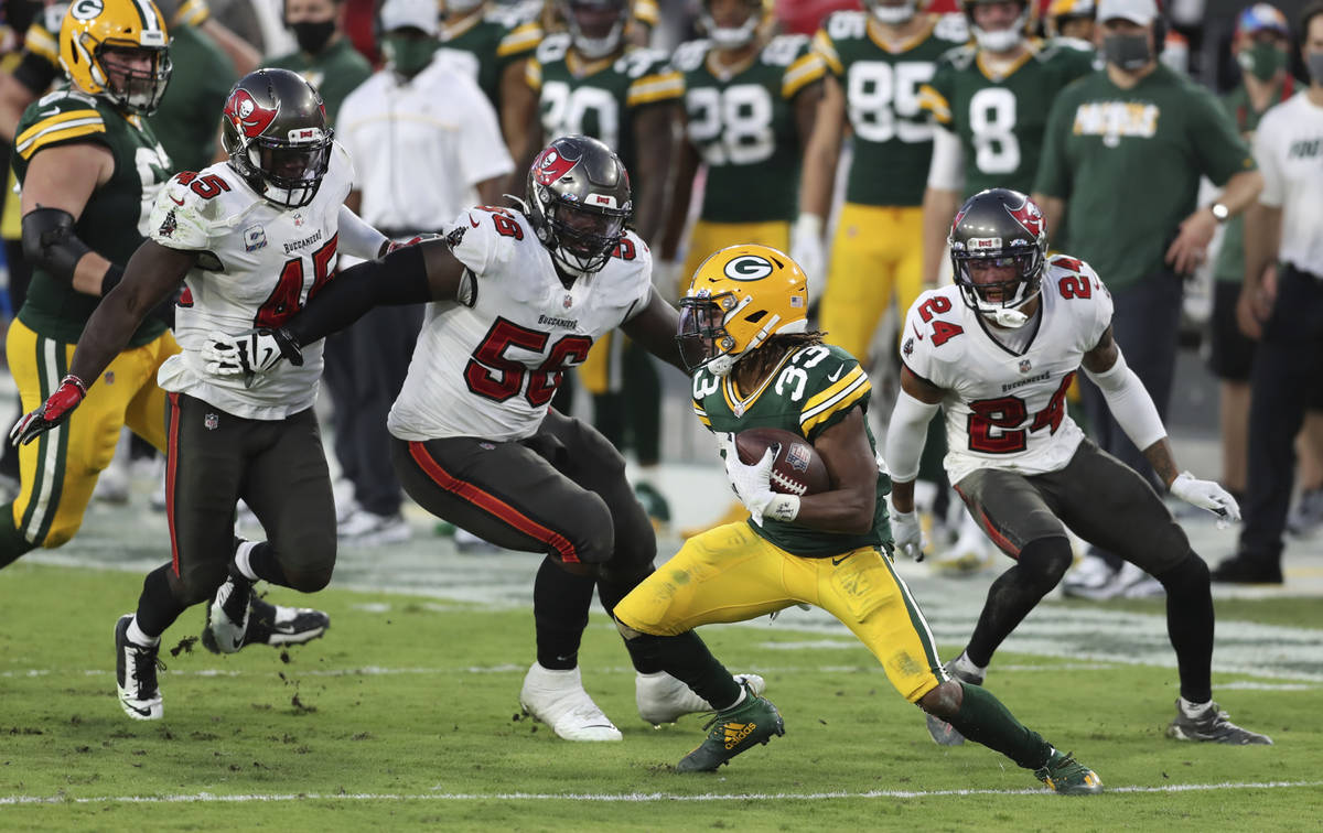 Green Bay Packers running back Aaron Jones (33) is surrounded by Tampa Bay Buccaneers inside li ...