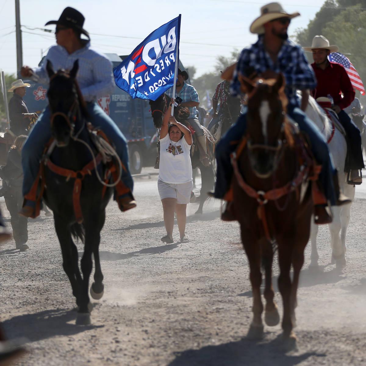 Adriana Martinez of Las Vegas, center, holds up a flag during a campaign parade for Assemblyman ...