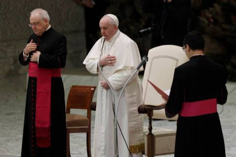 Pope Francis, center, makes the sign of the cross during his weekly general audience in the Pau ...