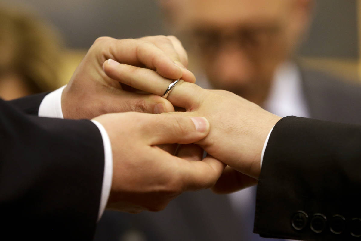 In a May 21, 2015, file photo, Mauro Cioffari, left, puts a wedding ring on his partner Davide ...