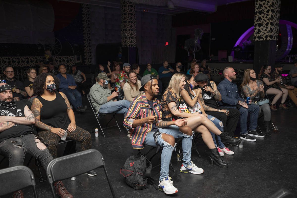Concert goers sit socially distanced while listening to Shanda & the Howlers preform at the ...