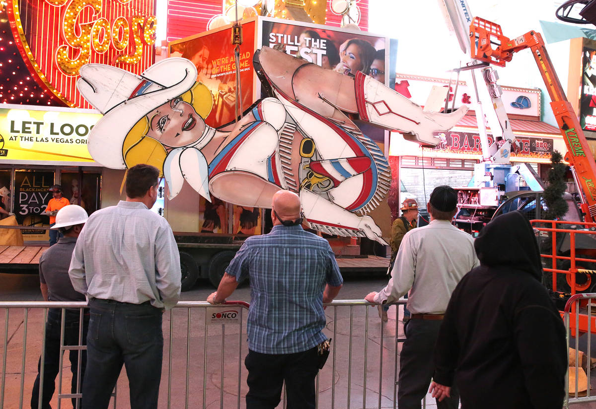People watch as workers remove the high-kicking Vegas Vickie on Fremont Street on Tuesday, June ...