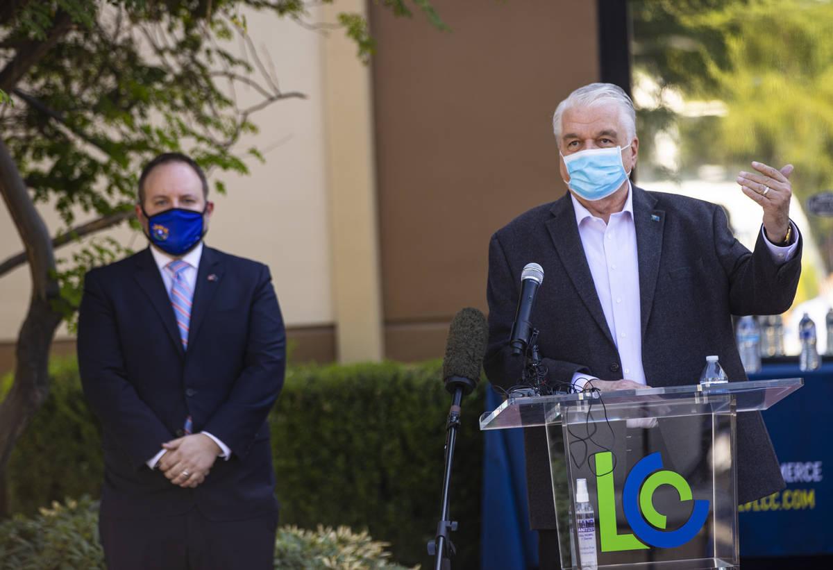 Gov. Steve Sisolak, right, speaks alongside Nevada State Treasurer Zach Conine during a press c ...