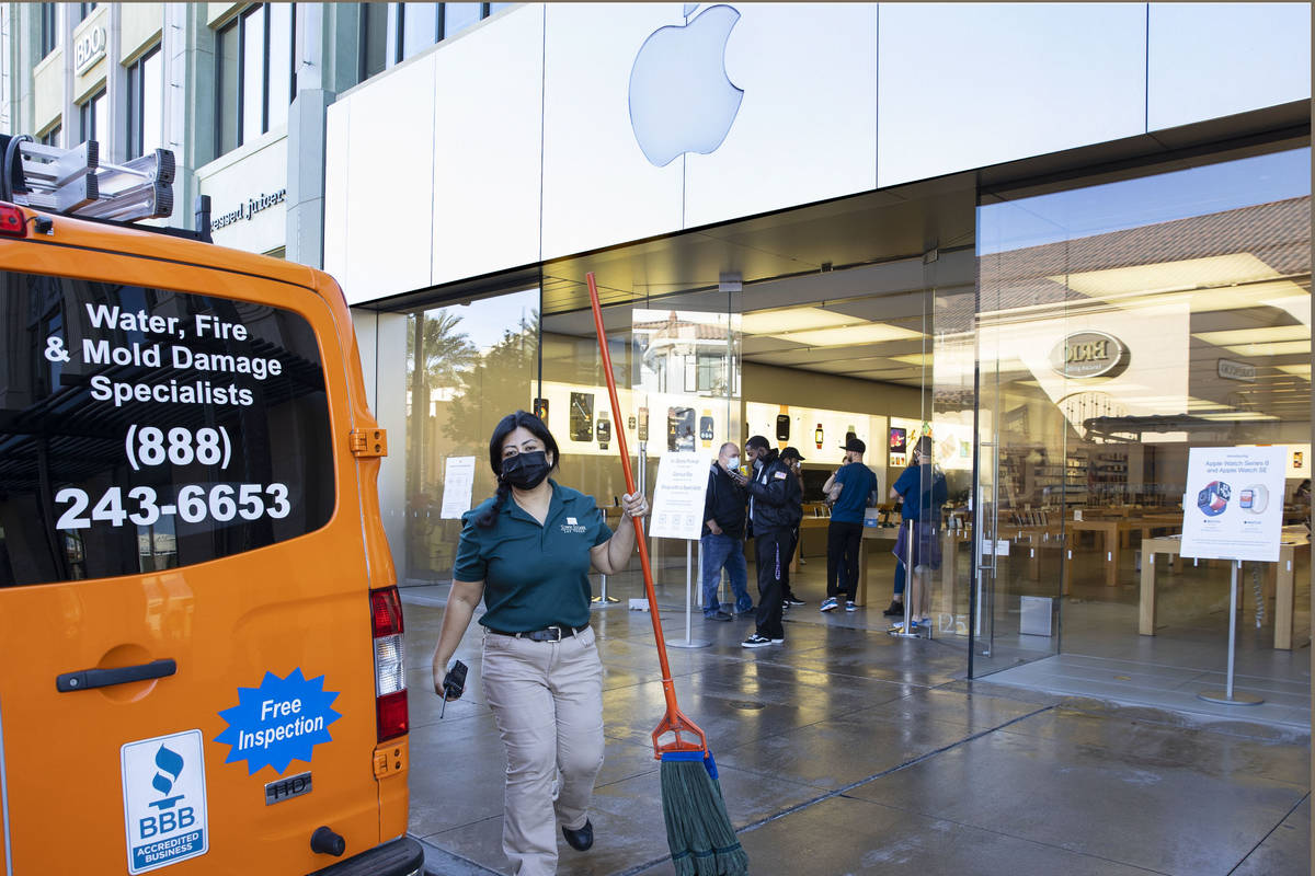 A worker mops a sidewalk outside of an Apple store after an electrical malfunction caused a fir ...