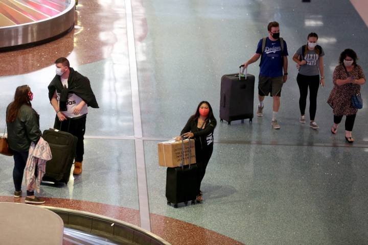 People leave baggage claim in Terminal 1 at McCarran International Airport in Las Vegas, Monday ...