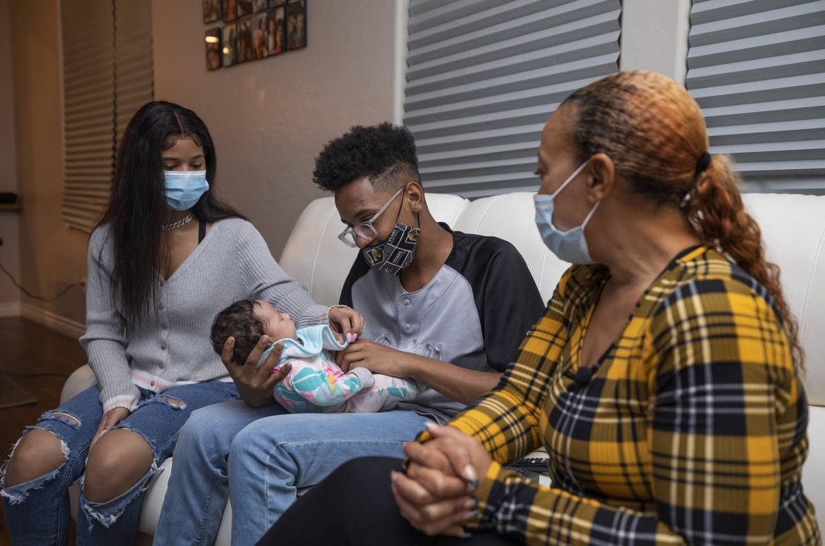 From left, Ebonee Levi, 17, Tavaras Chandler Jr., 14, holding 2-month old Zoie Chandler, and Da ...