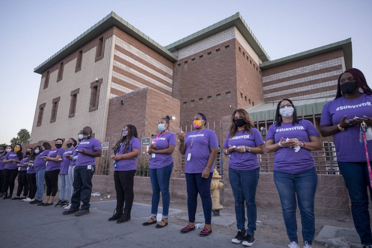 The Shade Tree staff members participate in a candlelight vigil to honor domestic violence vict ...