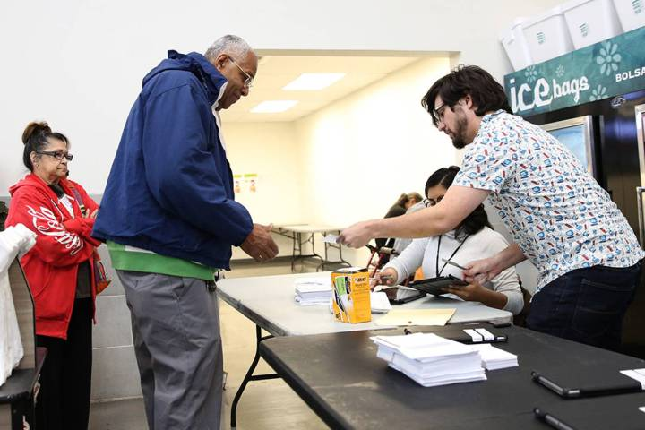 Nation Graca, right, site leader, hands out voting card to Reginald Bates of Las Vegas during t ...