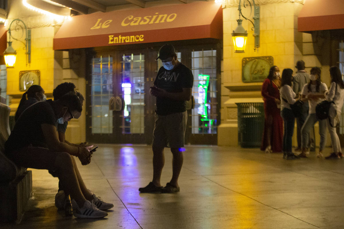 People linger outside Paris Las Vegas following a power outage, which resulted in a building ev ...