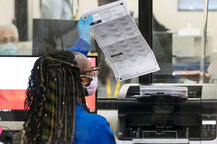 A Clark County election worker checks out a ballot as she prepares to scan it at the Election D ...
