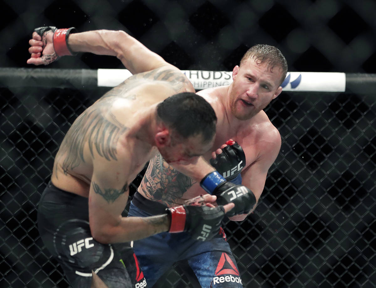 In this May 10, 2020, file photo, Tony Ferguson, left, falls backward after taking a punch from ...
