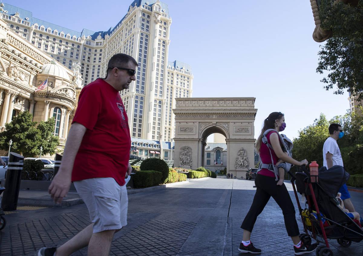 Tourist walk past Paris Las Vegas on Friday, Oct. 23, 2020, in Las Vegas. Hundreds of guests at ...
