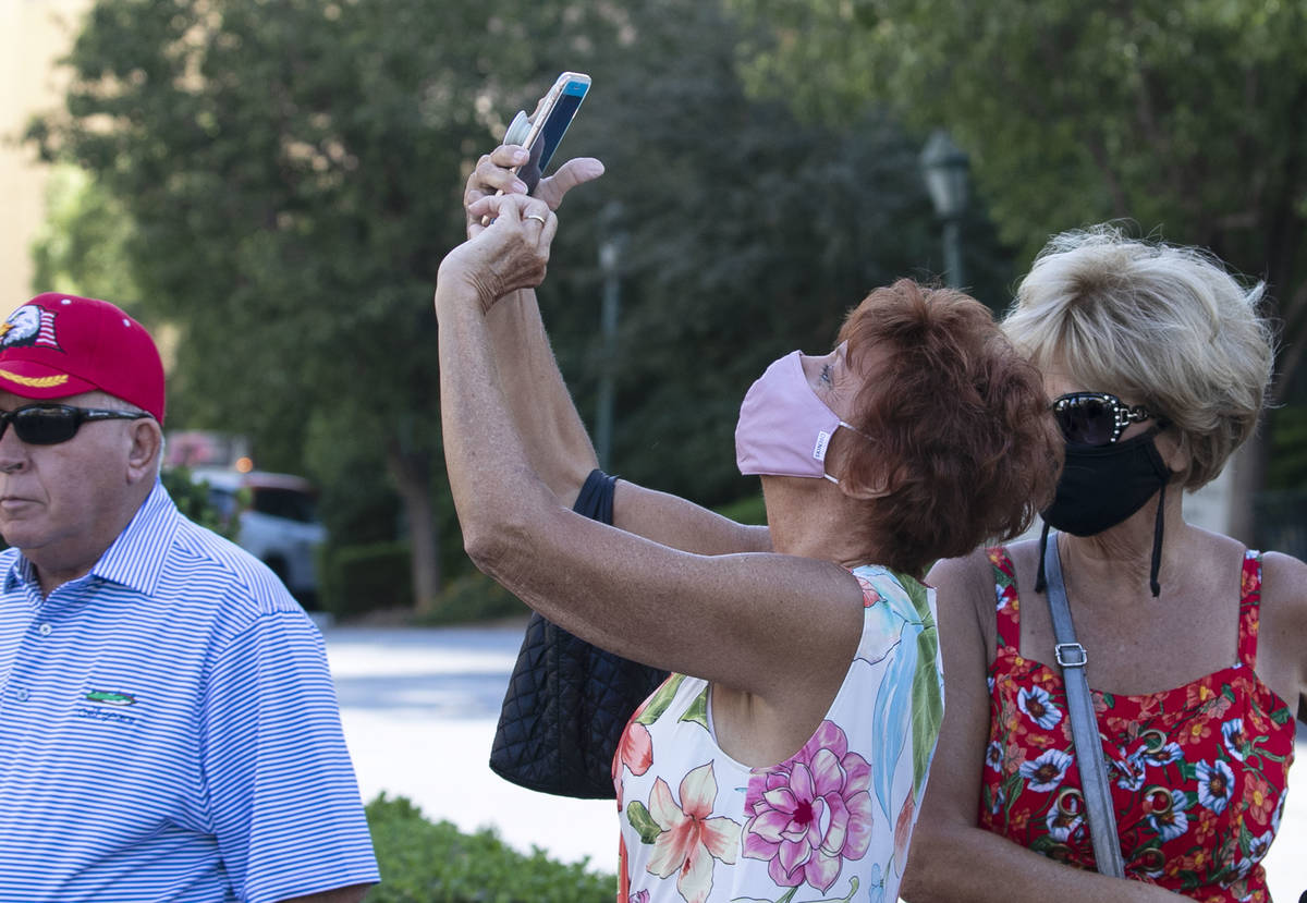 A tourist, who declined to give her name, takes a photo of the Eiffel Tower at Paris Las Vegas ...